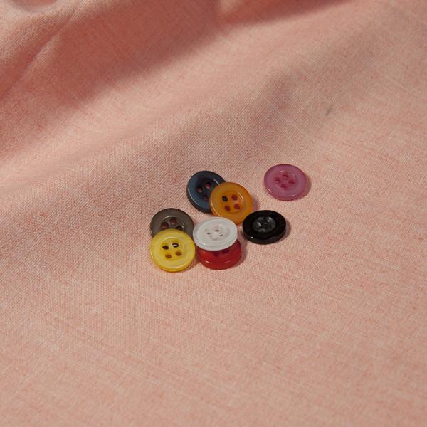 ボタンとピンク無地の生地